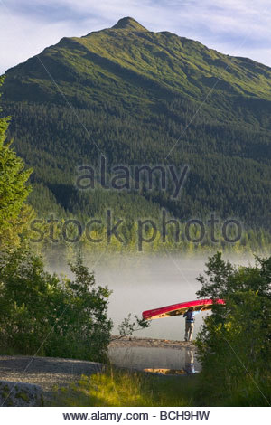 Person Carries Canoe to Mendenhall Lake SE AK Summer Tongass NF Morning - Stock Image