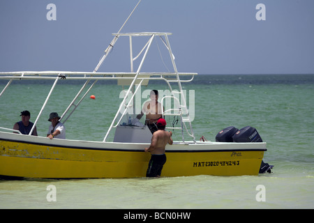 Fishing boat and men in shallow water, Caribbean Sea, Holbox island, Quintana Roo, Yucatán Peninsula, Mexico, - Stock Image