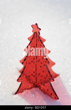 Red plastic Christmas tree decoration set in snow - Stock Image