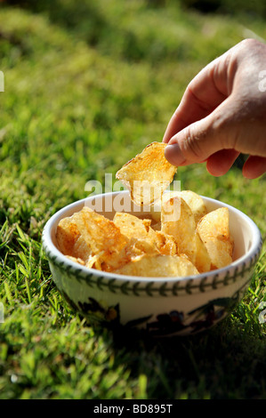 A woman picks up a crisp from a bowl during a summer barbeque - Stock Image