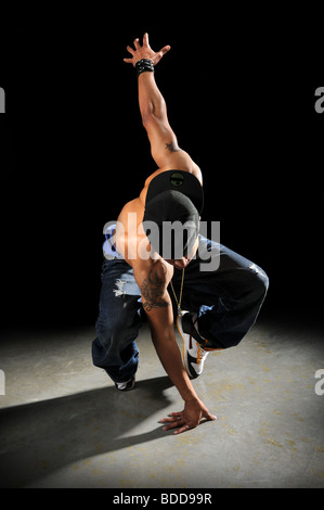 African American hip hop dancer performing over a dark background - Stock-Bilder