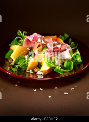 Peach and melon salad, with parma ham (prosciutto), almonds and lamb's lettuce. - Stock Image