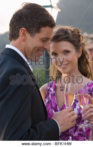 Well-dressed couple toasting champagne flutes - Stock Image
