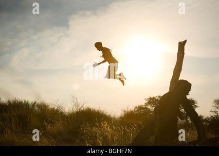 Bushmen tribal man jumping off fallen tree, Kalahari Desert, Namibia - Stock Image
