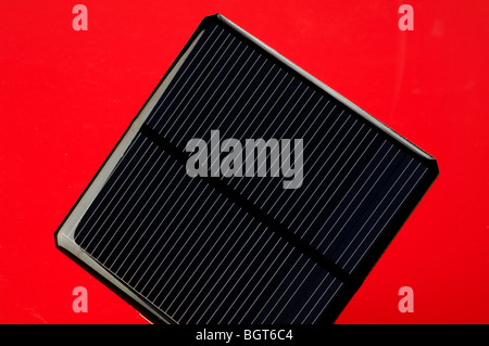 A square solar panel on a red background - Stock Image