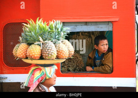 A woman selling fruit, a boy looking out of the window of a train, Hispaw, Shan State, Myanmar, Burma, Asia - Stock Image