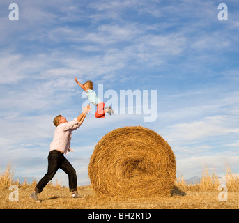 man catching boy jumping from hay bale - Stock-Bilder