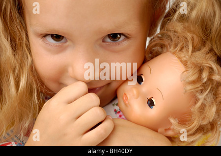 Expressive closeup portrait of a little girl with a doll - Stock Image