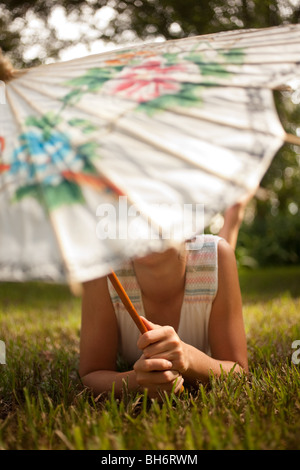 A girl relaxes on the lawn under her Chinese umbrella. - Stock Image