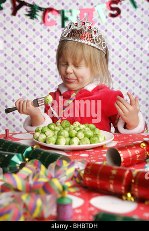A three year old sitting at a table with Christmas decorations and a plate full of sprouts pulling a face in disgust. - Stock-Bilder