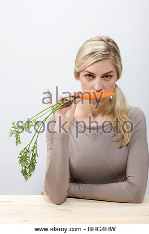 Woman holding a carrot - Stock Image