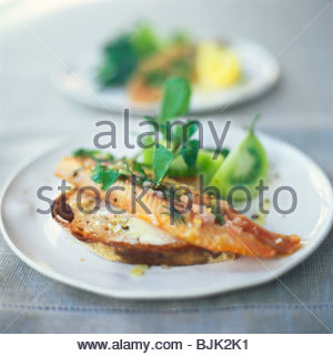 Smoked trout fillet on a slice of bread and butter - Stock Image