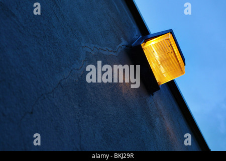 Safety light on cracked cement wall. - Stock Image