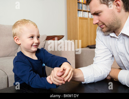 Son is arm wrestling whith his dad - Stock Image