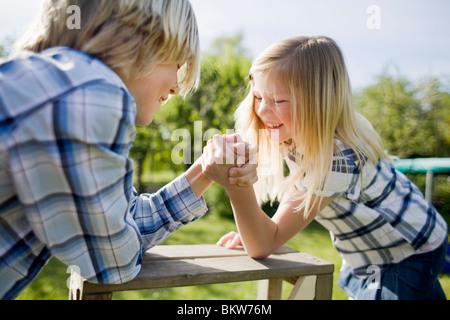 Siblings arm wrestling - Stock Image