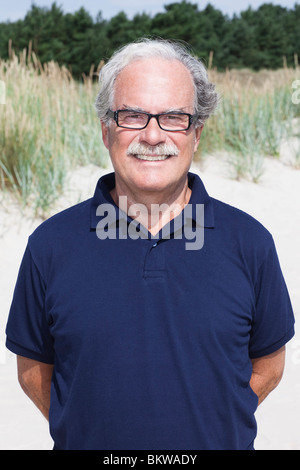 Lonely man standing on the beach - Stock Image