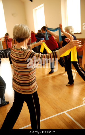 senior citizens participating in a low-impact aerobics class in a small village hall in west wales UK - Stock Image