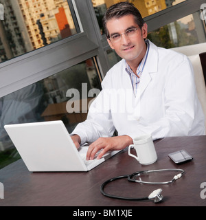 Portrait of a doctor working on a laptop - Stock Image