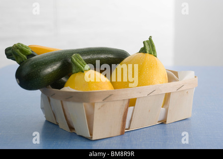 Zucchini and gold ball squash in basket - Stock Image