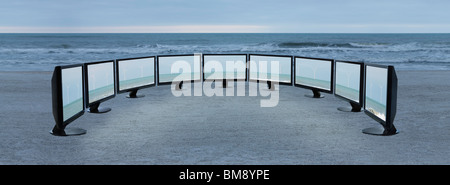 Flat screen televisions with images of wind turbines lined up on beach - Stock Image