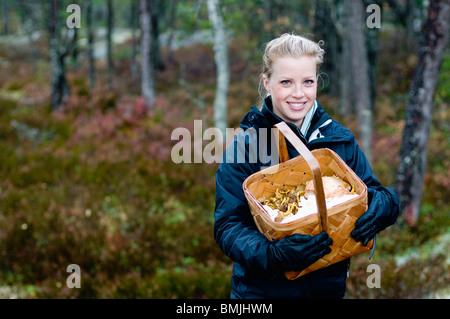Woman with mushrooms in basket - Stock Image