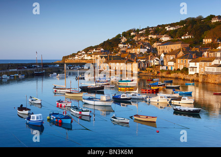 The first light of dawn catching the cottages along the waterfront, overlooking the picturesque Cornish Harbour - Stock-Bilder