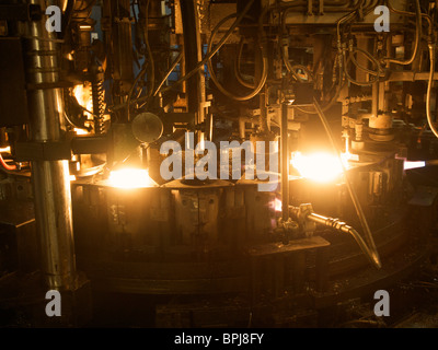 the production line of wine glasses where molten glass of around 1100 degrees centigrade is brought in the right - Stock Image