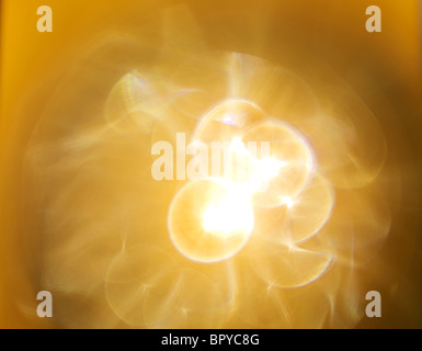Lens flare yellow star burst light that creates the nebulous feel - Stock Image