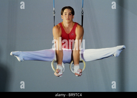 Male gymnast performing on the rings. - Stock Image
