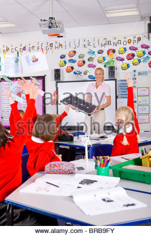 Teacher explaining solar panels to school children in classroom - Stock Image