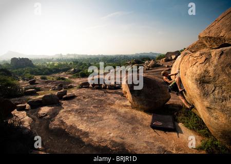 Male climber bouldering alone in vast boulderfield in Hampi, India. - Stock-Bilder