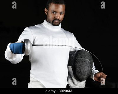 Portrait of a fencer wearing fencing uniform bending an epee in his hands. Isolated on black background - Stock Image