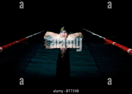 Professional swimmer taking breath during butterfly swimming - Stock-Bilder