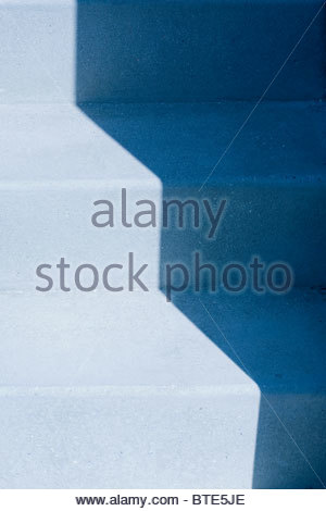 Highlight and shadow on blue staircase - Stock Image