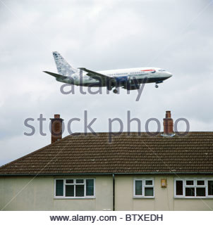 British Airways passenger plane landing at Birmingham Airport passing close to housing estate. Birmingham, UK. - Stock Image