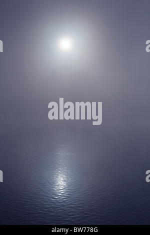 The sun reflecting on a blue misty lake - Stock Image