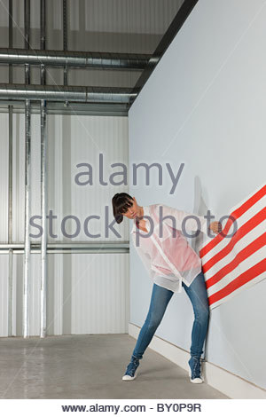 Young woman with striped wallpaper - Stock Image