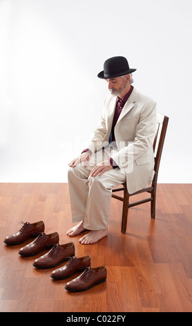 man sits with bare feet behind 5 identical shoes. - Stock Image