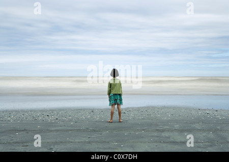 Girl in sharp focus looks at sea, with waves blurred by long exposure; black volcanic sand, Manawatu, New Zealand. - Stock Image
