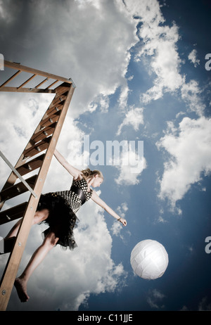 A teenage girl wearing a black and white polka dotted dress stands on a ladder while holding a white ball. - Stock-Bilder