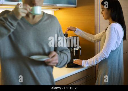 Couple enjoying coffee in kitchen - Stock Image