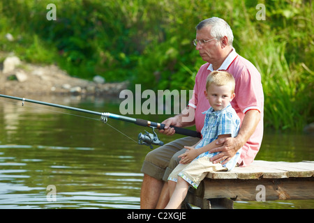 Photo of grandfather and grandson sitting on pontoon and fishing on weekend - Stock Image