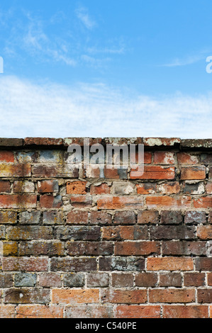 Old garden brick wall against a blue cloudy sky - Stock Image