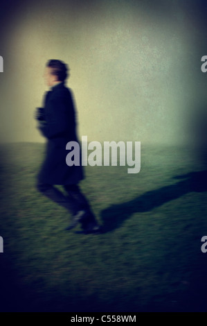 Blurred profile of a man running away - Stock Image