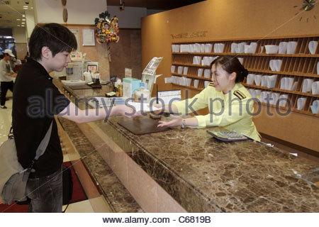 Japan Tokyo Ikebukuro Toyoko-Inn Ikebukuro Kita-guchi No.2 hotel lobby front desk clerk uniform guest Asian man - Stock Image