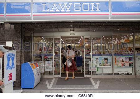 Tokyo Japan Ikebukuro Lawson Convenience Store front entrance Asian woman leaving shopper shopping kanji hiragana - Stock Image