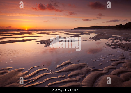 Sunset over the Atlantic Ocean, from the sandy shores of Bedruthan Steps beach, Cornwall, England. Spring (May) - Stock Image