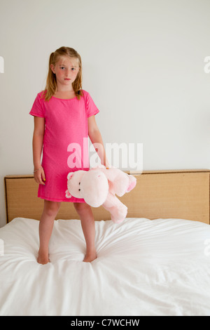 young girl on bed with stuffed animal - Stock-Bilder