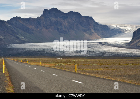 View of the Icelandic ring road leading to Skaftafell National Park and the Skaftafellsjokull glacier in southeast - Stock Image