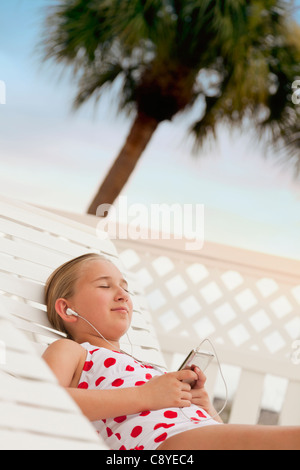 USA, Florida, St. Petersburg, Girl (10-11) with mp3 player relaxing on beach - Stock Image